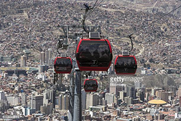 Travelers ride on red line Mi Teleferico cable cars above the city in La Paz, Bolivia, on Thursday, Sept. 8, 2016. Boliva's Mi Teleferico cable cars...