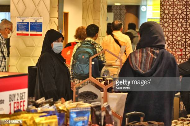 Travelers shop for duty free items while wearing face masks to protect from them the novel coronavirus while travelling through Abu Dhabi...