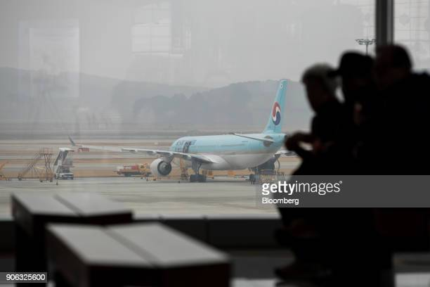 Travelers sit as a Korean Air Lines Co aircraft stands on the tarmac outside the terminal 2 building at Incheon International Airport in Incheon...