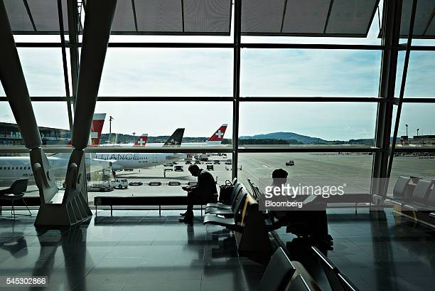 Travelers sit at the gate awaiting their departure at Zurich Airport operated by Flughafen Zuerich AG in Zurich Switzerland on Wednesday July 6 2016...