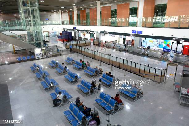 Travelers sit with their luggage inside the UTapao International Airport in Ban Chang district Rayong Province Thailand on Tuesday Sept 4 2018...