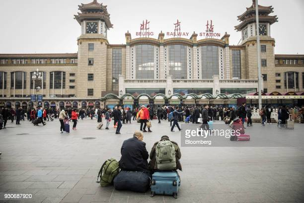 Travelers sit with their luggage outside Beijing Railway Station in Beijing China on Wednesday March 7 2018 China's consumer inflation surged to the...