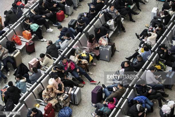 Travelers sit with their luggage while waiting in the main hall of the Shanghai Hongqiao Railway Station in Shanghai China on Wednesday Jan 30 2019...