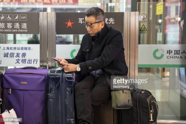 A travelers sits with his luggage while waiting in the main hall of the Shanghai Hongqiao Railway Station in Shanghai China on Wednesday Jan 30 2019...