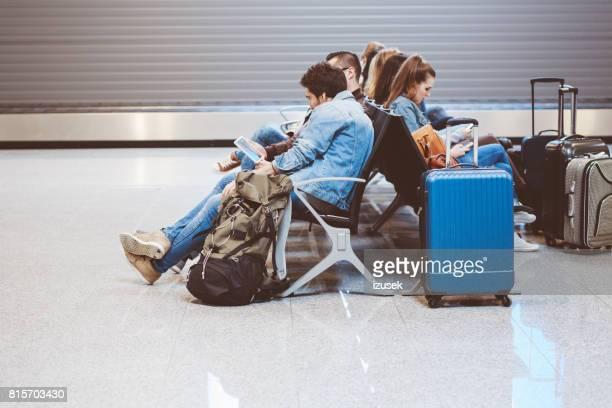 viajantes, sentado no aeroporto terminal com telefone móvel e bagagem - izusek - fotografias e filmes do acervo
