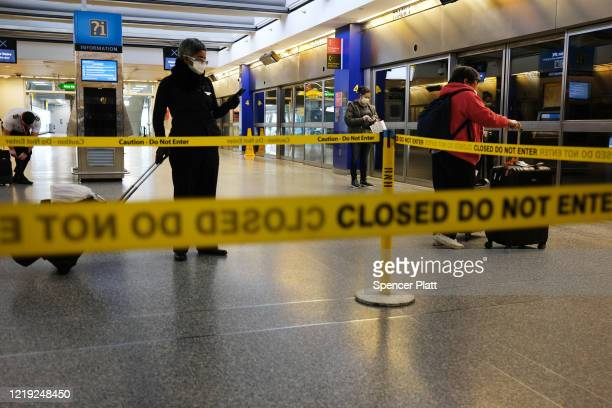 Travelers, some in protective gear, walk through John F. Kennedy Airport as it stands mostly empty due to the ongoing cutbacks in travel because of...