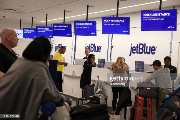 Travelers speak to representatives at the JetBlue Airways Corp check in counter at John F Kennedy International Airport during Winter Storm Quinn in...