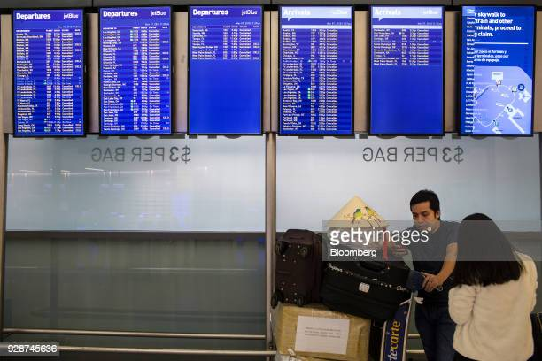 Travelers stand beneath JetBlue Airways Corp departure information screens at John F Kennedy International Airport during Winter Storm Quinn in New...