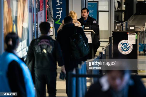 Travelers stand in line at a Transportation Security Administration checkpoint at Terminal B in LaGuardia Airport in the Queens borough of New York...