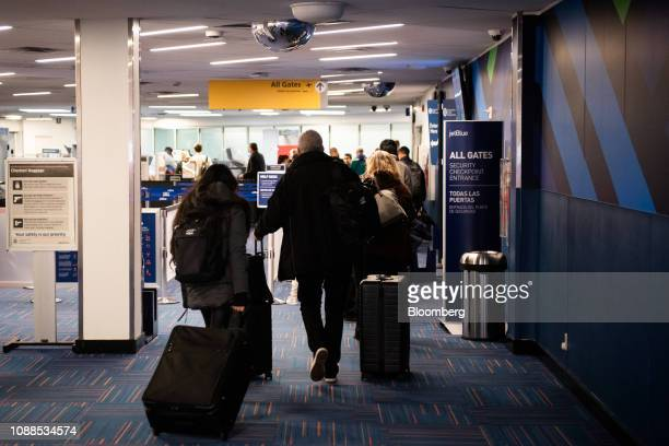 Travelers stand in line at a Transportation Security Administration checkpoint at LaGuardia Airport in the Queens borough of New York US on Friday...