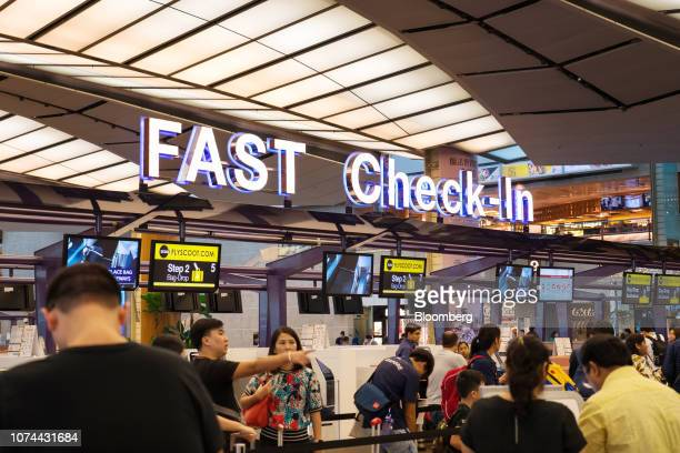 Travelers stand in line at fast checkin counters in the departure hall at Terminal 2 of Changi Airport in Singapore on Thursday Dec 13 2018...