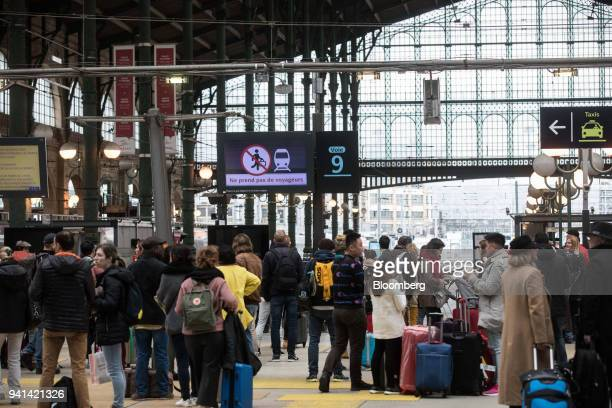 Travelers stand on a platform as they wait for a train during industrial strike action by railway workers and other labor union members at Gare du...