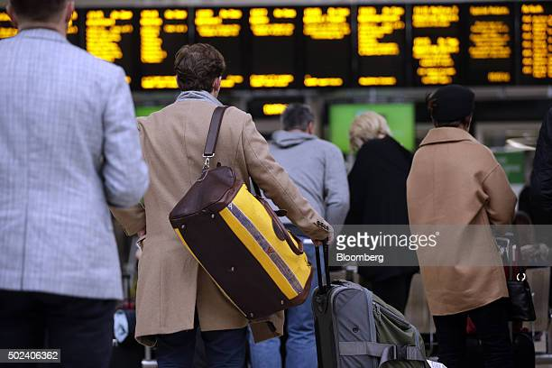 Travelers stand with their luggage in the departure hall of Paddington railway station in London UK on Thursday Dec 24 2015 UK stocks were little...
