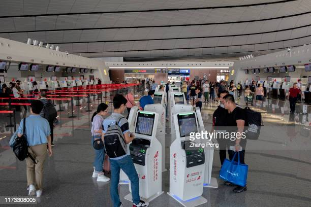 Travelers type boarding tickets on selfservice machines in Beijing Daxing International Airport which officially began to operate on September 25th...