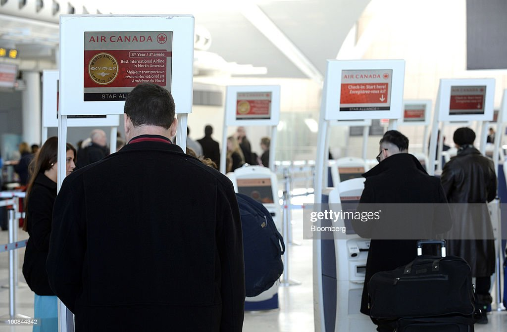Travelers use Air Canada check-in kiosks at Pearson International Airport in Toronto, Ontario, Canada, on Wednesday, Feb. 6, 2013. Air Canada, the country's biggest carrier, is scheduled to announce quarterly earnings data on Feb. 7. Photographer: Aaron Harris/Bloomberg via Getty Images