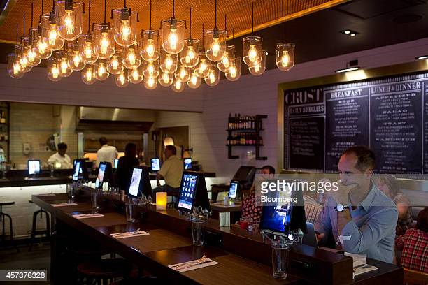 Travelers use newly installed Apple Inc iPads to order food and surf the web at Crust restaurant in the Delta Air Lines Inc Terminal D at LaGuardia...