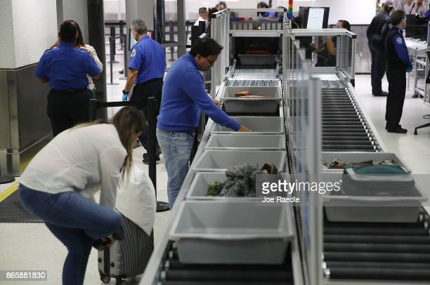 Travelers use the automated screening lanes funded by American Airlines and installed by the Transportation Security Administration at Miami...