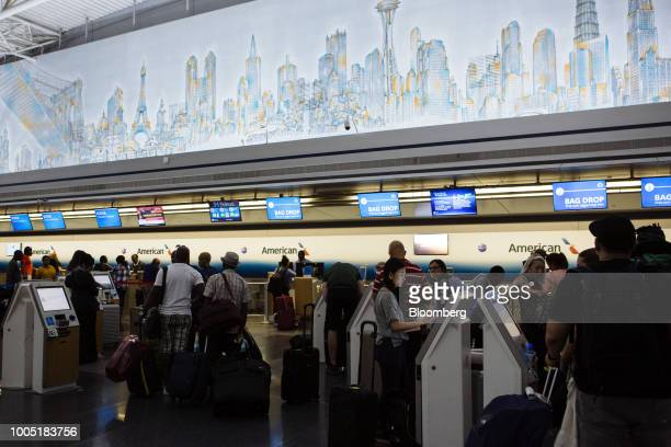 Travelers use the self checkin kiosks inside the American Airlines Group Inc Terminal 8 at John F Kennedy International Airport in New York US on...
