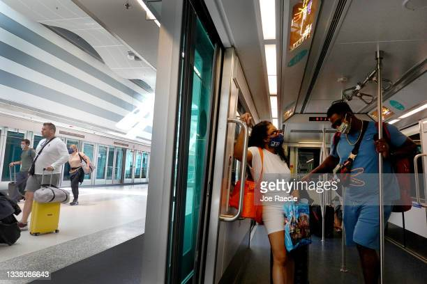Travelers use the tram as they make their way through the Miami International Airport before starting the Labor Day weekend on September 03, 2021 in...