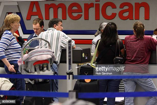 Travelers wait at the American Airlines ticket counter April 9 2008 at the Dallas Fort Worth International Airport in Irving Texas American Airlines...