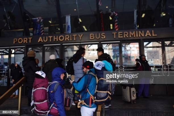 Travelers wait at the entrance of New York Port Authority after it was reopened following an explosion in Manhattan borough of New York City United...
