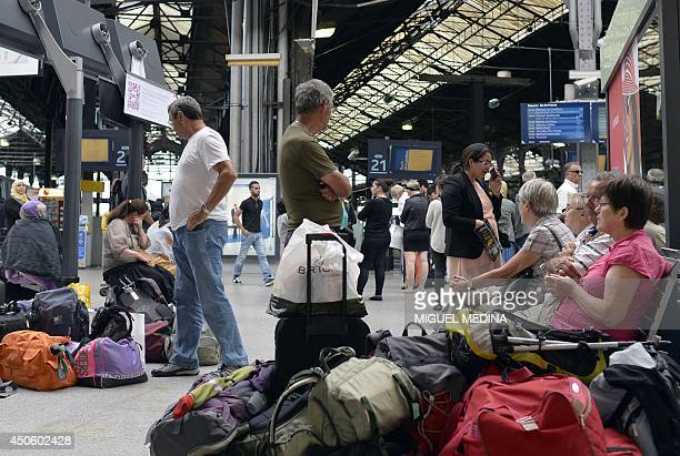 Travelers wait at the Gare Saint Lazare train station in Paris during a strike by SNCF railway company workers on June 16 2014 The strike is expected...