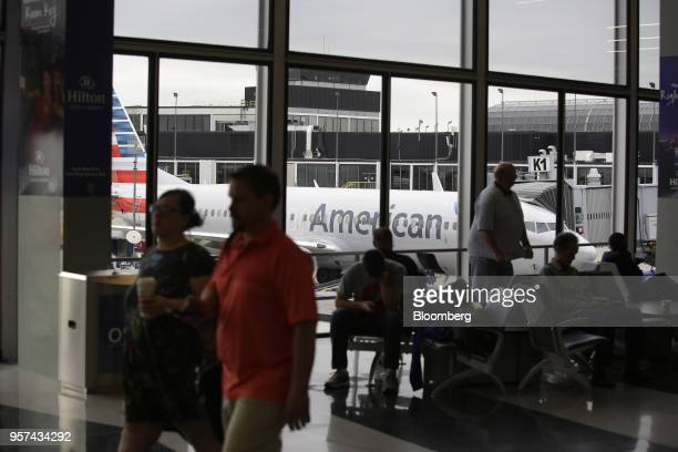 Travelers wait for flights as an American Airlines Group Inc plane sits during an event to mark the opening of five new gates inside Terminal 3 at...