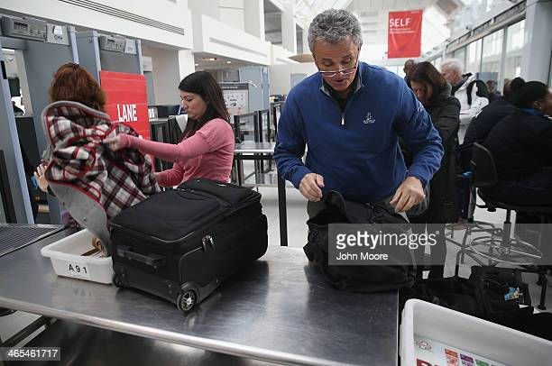 Travelers wait for screening at a special TSA Precheck lane at Terminal C of the LaGuardia Airport on January 27 2014 in New York City Once approved...