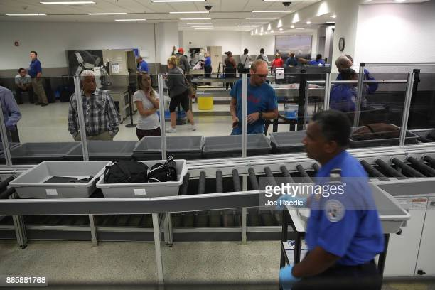 Travelers wait for their bags at an automated screening lane funded by American Airlines and installed by the Transportation Security Administration...
