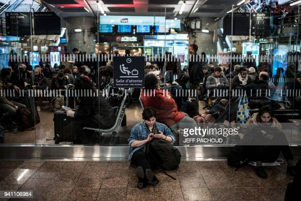 Travelers wait for their trains at the Lyon Part-Dieu railway station, on the first evening of a two days strike, on April 2, 2018 in Lyon. France...