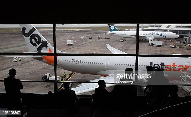 Travelers wait in a departure lounge as a Jetstar Airways aircraft front and an Air New Zealand Ltd aircraft stand on the tarmac at Auckland...