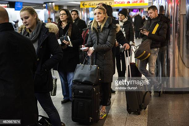 Travelers wait in a line at La Guardia Airport during a winter storm on February 2, 2015 in the Queens borough of New York City. The snowstorm, which...
