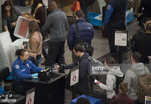 Travelers wait in line at a security screening checkpoint inside the airport terminal at Ronald Reagan Washington National Airport in Arlington...