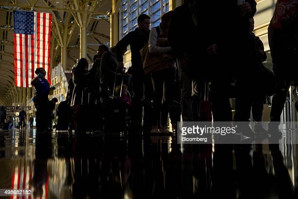 Travelers wait in line before going through Transportation Security Administration screening at Ronald Reagan National airport in Washington DC US on...