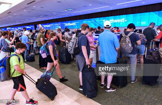 Travelers wait in line to check in at the Southwest Airlines ticket counter at Orlando International Airport on the Friday before Memorial Day. As...