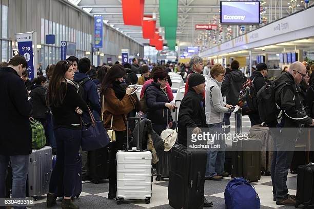 Travelers wait in line to checkin for flights at O'Hare International Airport on December 23 2016 in Chicago Illinois O'hare International Airport is...