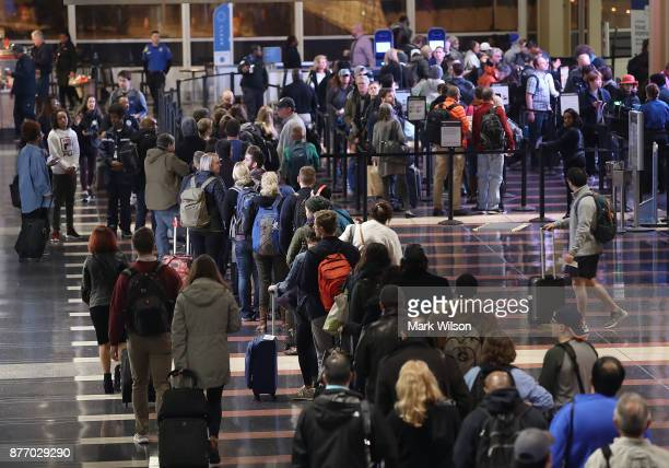 Travelers wait in line to go through the security area at Reagan National Airport on November 21 2017 in Arlington Virginia Heavy air travel is...