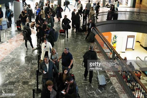 Travelers wait in line to inquire about the latest on Amtrak service suspension March 2 2018 at Union Station in Washington DC Amtrak has cancelled...