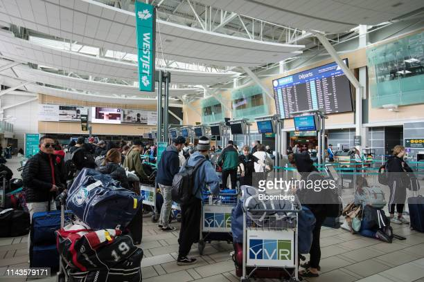 Travelers wait in the WestJet Airlines check-in area at Vancouver International Airport in Richmond, British Columbia, Canada, on Monday, May 13,...