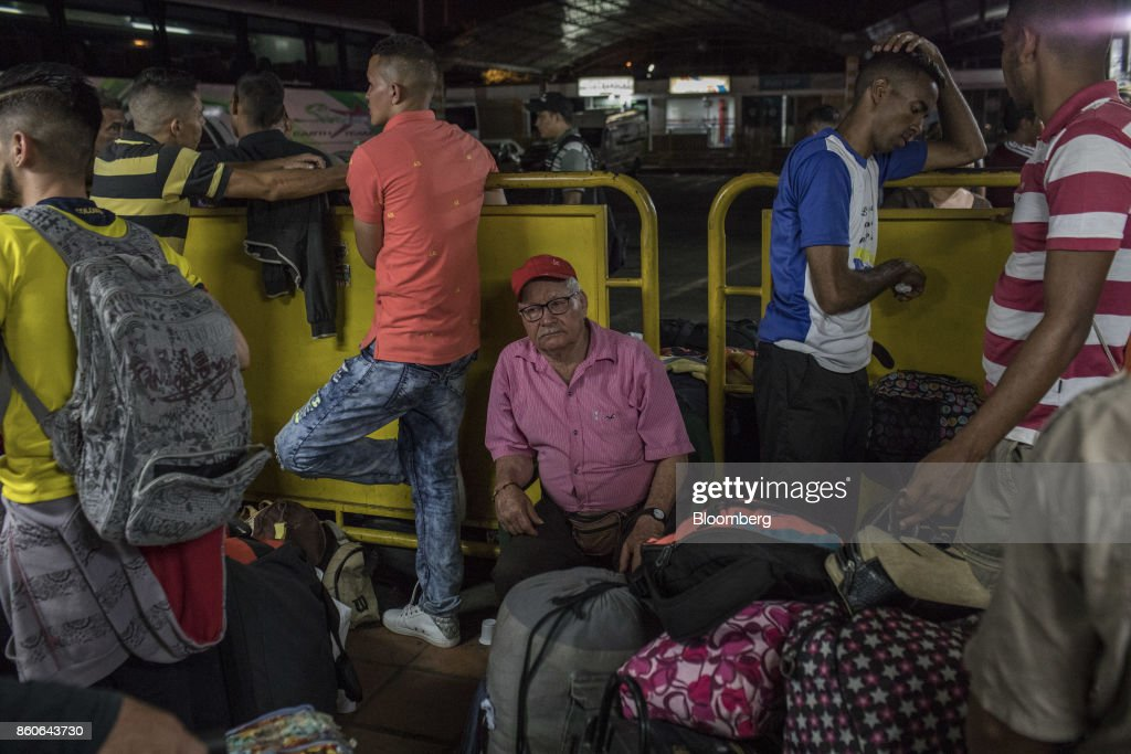 Travelers wait to board buses at a terminal in Cucuta, Colombia, on Thursday, Sept. 21, 2017. For weeks, Venezuelans have been flocking by the busload to San Antonio del Tachira, a border town of some 62,000 residents, fleeing as President Nicolas Maduro consolidates autocratic power. According to Colombia's migration authority, the number of foreigners entering Cucuta, the first major city across the bridge, more than doubled this summer. Photographer: Nicolo Filippo Rosso/Bloomberg via Getty Images