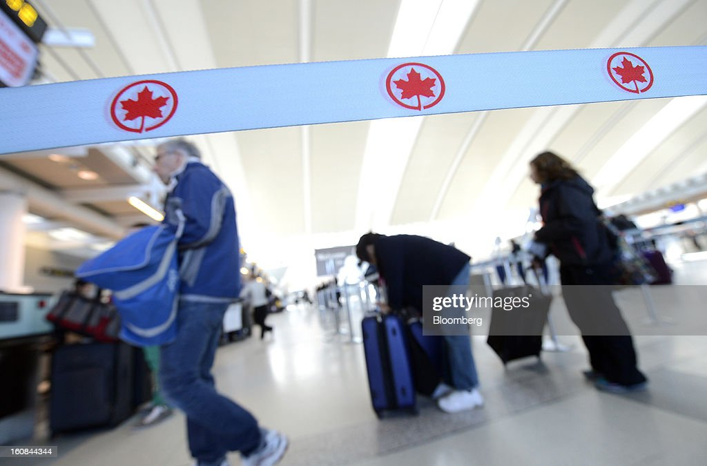 Travelers wait to check-in at the Air Canada counter at Pearson International Airport in Toronto, Ontario, Canada, on Wednesday, Feb. 6, 2013. Air Canada, the country's biggest carrier, is scheduled to announce quarterly earnings data on Feb. 7. Photographer: Aaron Harris/Bloomberg via Getty Images