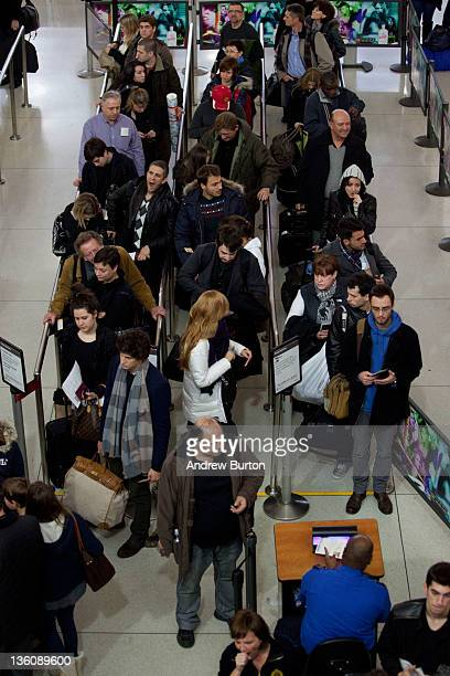 Travelers wait to go through a security screening in Terminal One of John F Kennedy Airport on December 23 2011 in New York City Port Authority of...