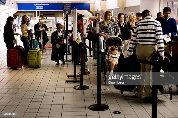 Travelers wait to pass through a security checkpoint at DallasFort Worth International Airport in Dallas Texas US on Wednesday Nov 26 2008 The US...
