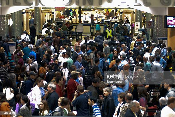 Travelers wait to pass through a security checkpoint inside HartsfieldJackson International Airport in Atlanta Georgia US on Wednesday Nov 21 2007...