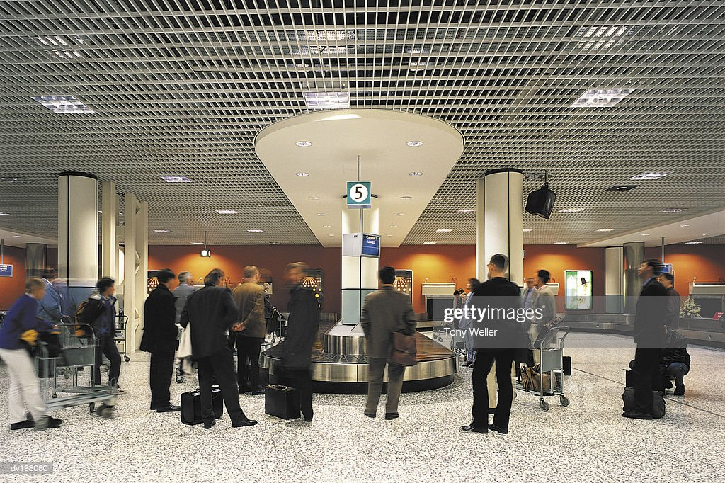 Travelers waiting at baggage claim for their luggage : Stock Photo