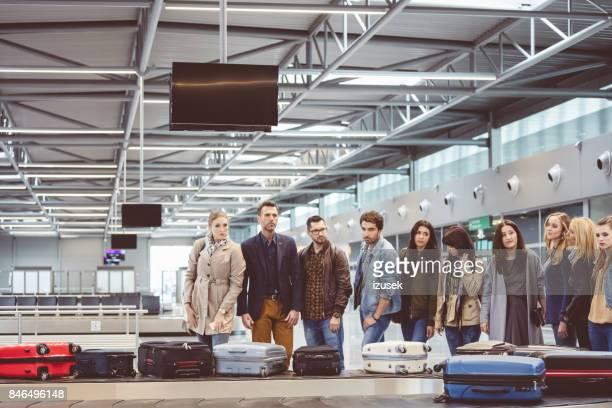 Reisende warten auf Gepäck bei der Gepäckausgabe behaupten Bereich