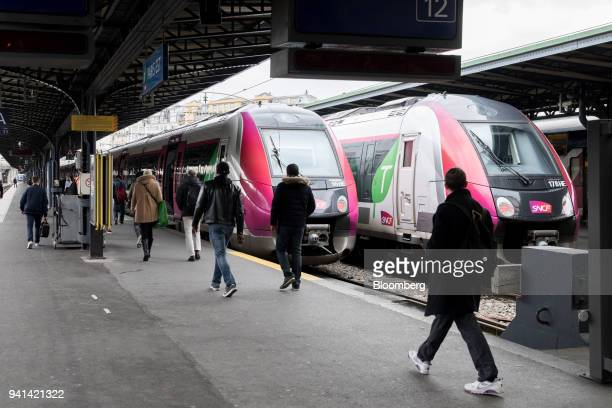 Travelers walk along a platform as a pair of trains operated by French national railway operator Societe Nationale des Chemins de Fer stand during a...