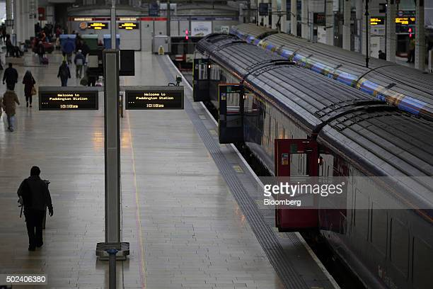 Travelers walk along a platform as passenger trains stand at Paddington railway station in London UK on Thursday Dec 24 2015 UK stocks were little...