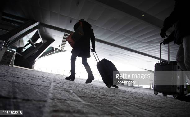 Travelers walk amid snow and wind to the transit center at Denver International Airport on November 26 2019 in Denver Colorado Flights were delayed...