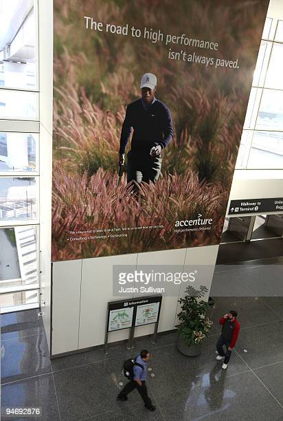 Travelers walk by an advertisement for Accenture that features professional golfer Tiger Woods December 17 2009 at San Francisco International...